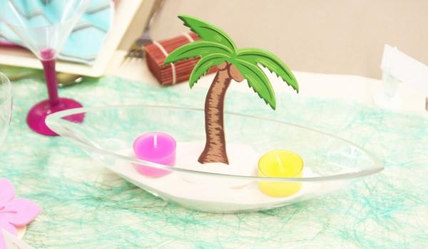 Composition réalisée avec un palmier, du sable et des bougies